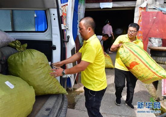 7月27日,在融水苗族自治县杆洞乡党鸠村木耳种植基地,螺蛳粉企业员工将收购的木耳搬上车