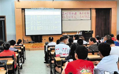 ▶在南宁三中中考招生报名点,考生与家长关注着大屏幕实时滚动播出的中招公示信息