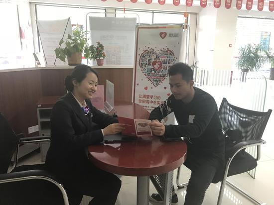 """网点工作人员为客户宣传""""邮爱公益日""""活动"""