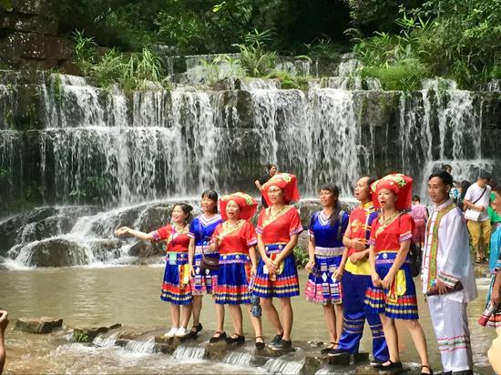 九龙瀑布景区里穿着壮族服饰的青年男女正在唱着山歌 莫扬娇/摄