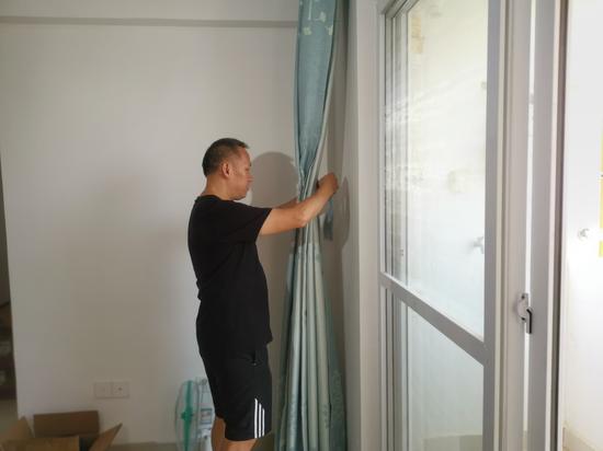 隆江老师在新居中整理窗帘。新浪广西 黄媛/摄