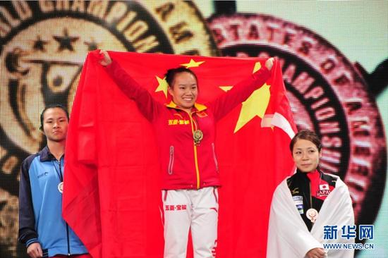 11月21日,中国选手蒋惠花(中)在颁奖仪式上。当日,在美国休斯敦举行的2015年世界举重锦标赛女子48公斤级比赛中,中国选手蒋惠花以198公斤的总成绩夺冠。 新华社记者张永兴摄