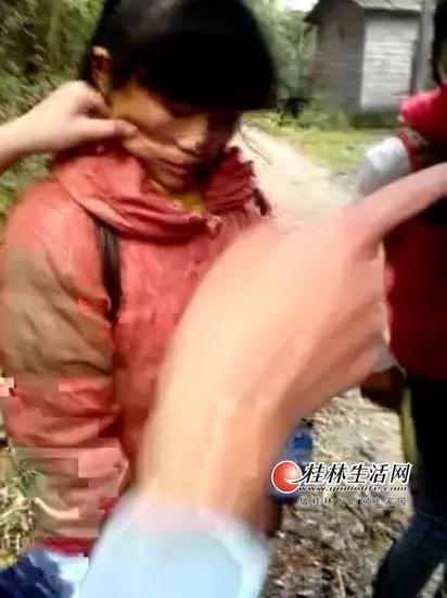 灌阳打人事件中,有人捏被打女孩的脸。(视频截图)