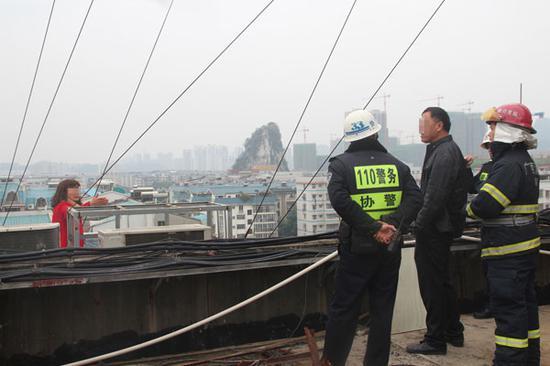 民警和消防官兵正劝庞某回到安全地带,中间站立的男子为其丈夫王某。 今报记者 石红星摄