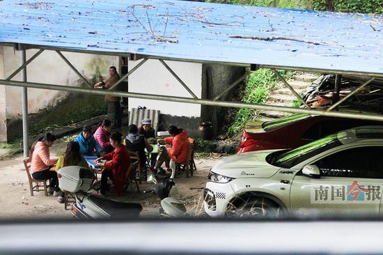 3月15日,记者在融水苗族自治县四荣乡四合村看到,村民聚在新买的小车旁打牌、打麻将