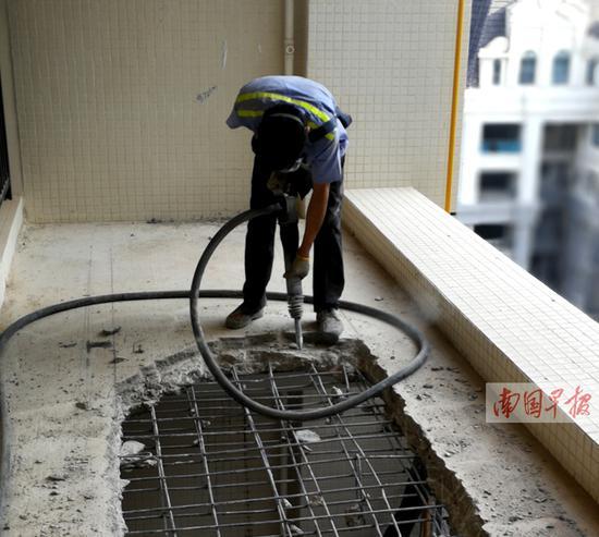 """施工人员正在拆除违规建设的""""阳台""""。 记者 李俭芹摄b"""