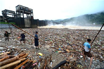 发洪水财?融水村民冒生命危险在泄洪坝口打捞木材