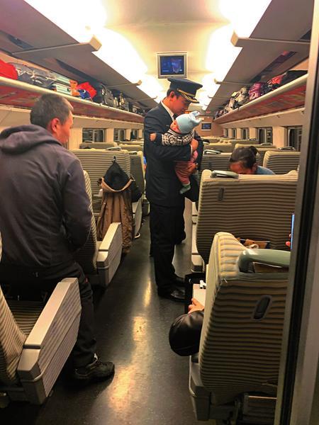 """陈凯变""""奶爸""""帮乘客照顾婴儿。(戴佩芸摄)"""