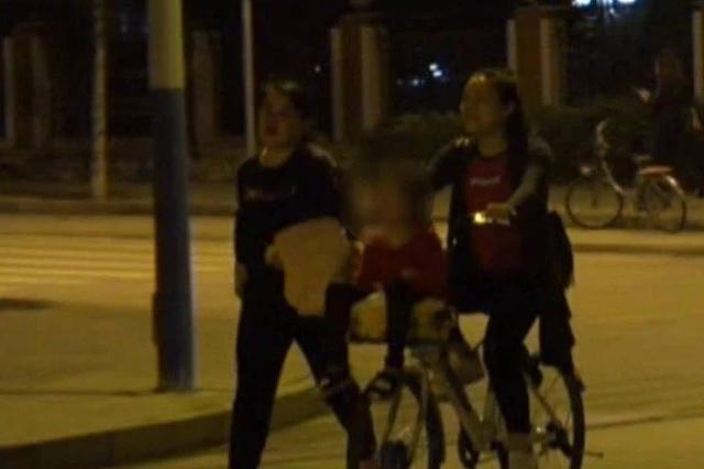 危险!市民把孩子放在共享单车篮子里骑行(图)