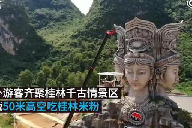 桂林:游客挑战在50米高空吃米粉 拉升后恐高放弃