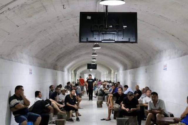 民众在柳州市马鞍山人防工程避暑纳凉点内看电视。 覃诗明 摄