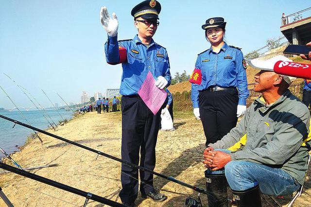 城管队员向垂钓者发放爱护邕江宣传单本报记者黎兆齐摄