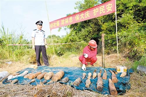 ◀工作人员将废旧炮弹轻轻放在地上