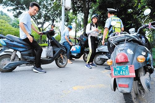 ▲交警查获在南宁市区行驶的悬挂桂C牌照电单车 本报记者 宋延康 摄
