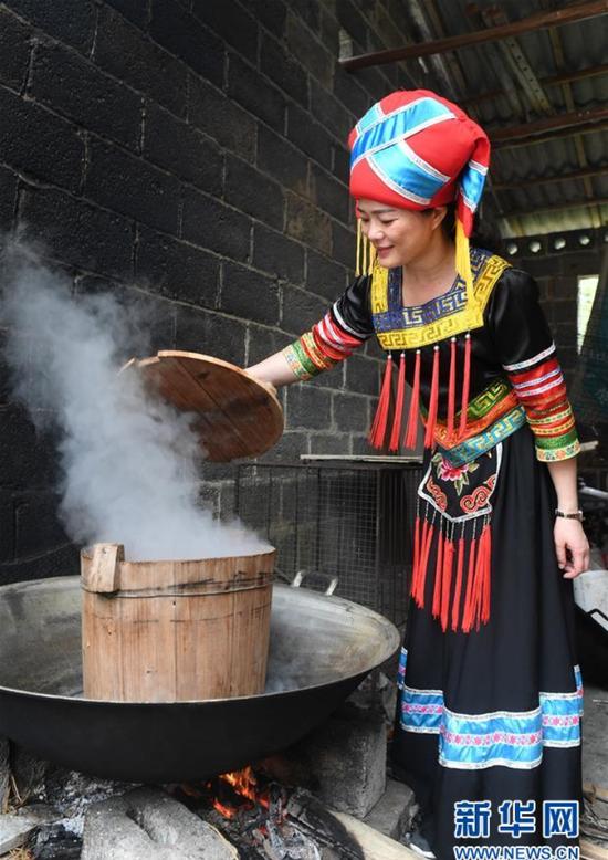 3月25日,在广西上林县巷贤镇,一名壮族女子在蒸制五色糯米饭。 新华社记者 陆波岸 摄