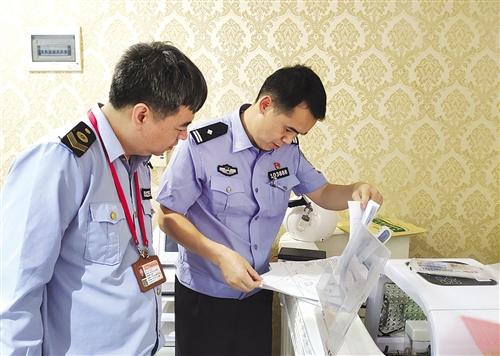 ▲ 执法人员查验顾客登记材料 本报通讯员 陈西津 摄