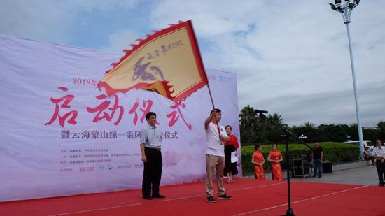 蒙山县人大常委会主任何健向采风团作家代表杨克授旗