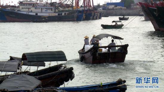 9月18日傍晚,在广西北海市侨港镇电建渔港,一艘卸载完毕的小渔船驶离港口。