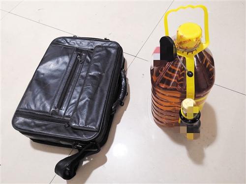 ▼班某作案使用的公文包和盗窃得来的花生油 本报记者 潘国武 摄