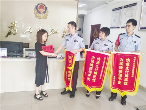 女出纳向警方送上锦旗表示感谢 本报记者 黎兆齐 摄