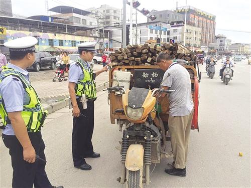 拉载着木材的无号牌黄色三轮摩托车被交警拦停(交警供图)