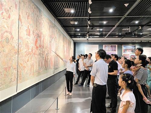 观众们仔细听讲解员解说壁画的绘画细节和背后寓意 本报记者 陈蕾 摄
