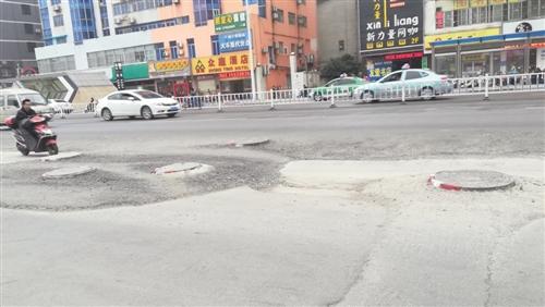 市民骑车路过多个凸出地面的井盖 本报记者 韦薇 摄