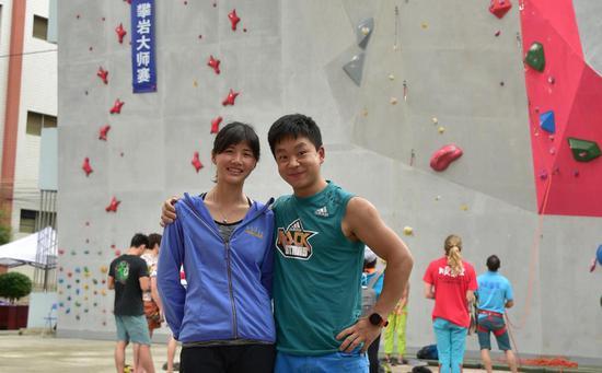 参赛选手刘加与黄伟君情侣攀岩档在攀岩大师赛人工岩壁赛场前合照/陆丽红摄