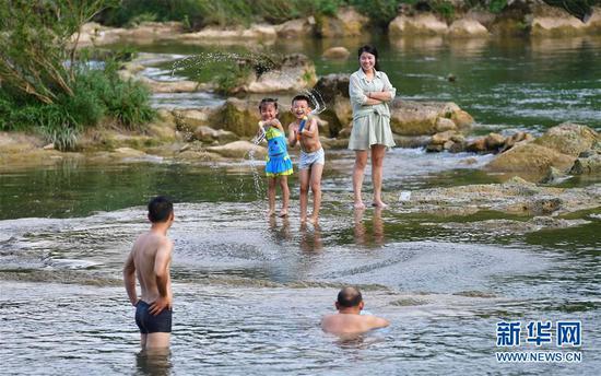 在广西鹿寨县中渡古镇响水瀑布景区,游客在响水河里戏水消暑(8月9日摄)