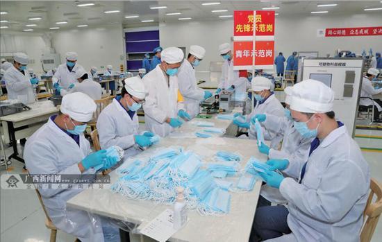 2月18日,在新成立的广西宝菱康医疗器械有限公司,员工正在加紧生产口罩。该公司仅用3天就完成自产第一批民用防护口罩。记者 梁凯昌 摄