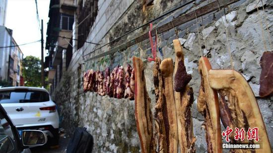 居民直接把腊肉和腊肠挂在路边停车位的旁边。王以照 摄