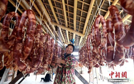 在亚洲真人娱乐平台三江侗族自治县丹洲镇丹洲村,村民梁玉华在整理制作好的腊肠。吴练勋 摄