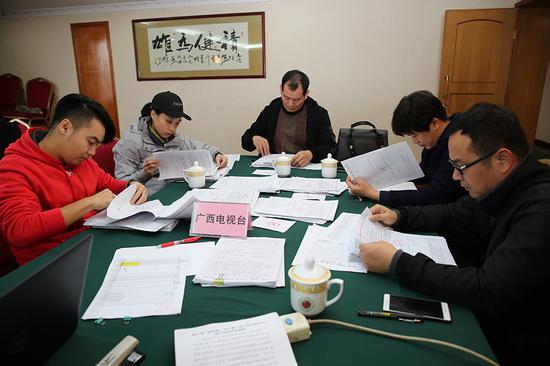 評審小組認真審閱每一份幫扶申請表(王云濤攝)