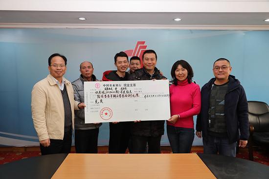 广西福彩中心副主任梁卫(左一)向部分中奖代表颁发奖金支票(王云涛摄)