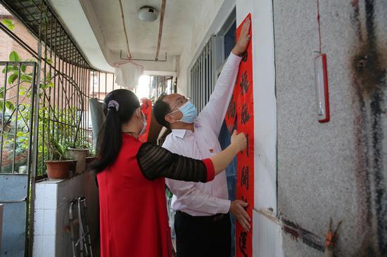 廣西福彩中心黨員代表與社區工作人員一起為困難群眾貼上喜慶的春聯