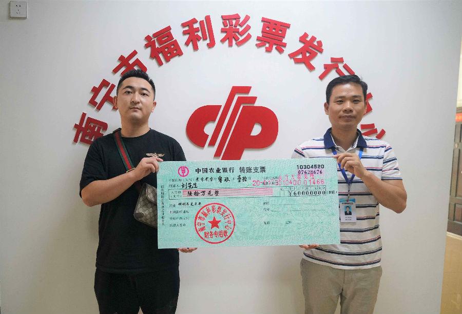 图为:市福彩中心工作人员为刘先生(左)颁奖