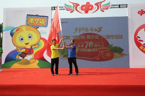 南宁市福彩中心负责人将健步走旗帜交回到广西福彩中心副主任梁卫手中