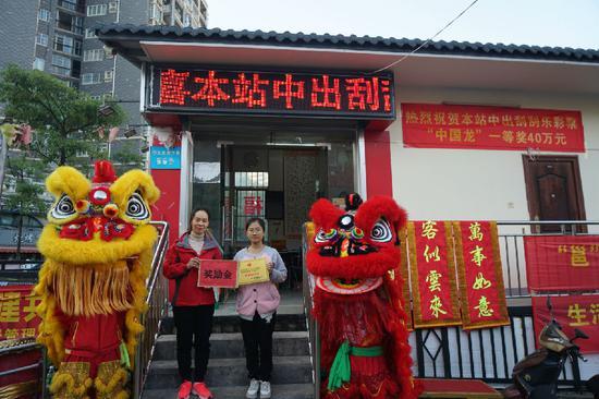 图为南宁市福彩中心工作人员为中奖投注站业主(右)颁发奖励金和牌匾