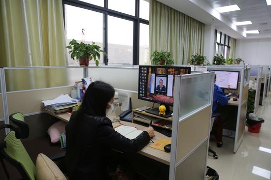 广西福彩中心员工在工作岗位上通过手机或电脑参加视频会议