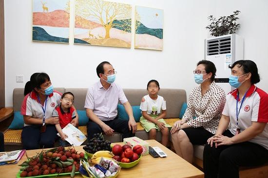 """朱学庆一行在""""模拟家庭""""慰问困境儿童和""""护理妈妈""""——梁靖浩摄"""