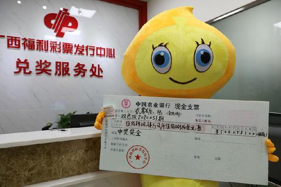 图为王先生(化姓)持中奖彩票和奖金支票合影