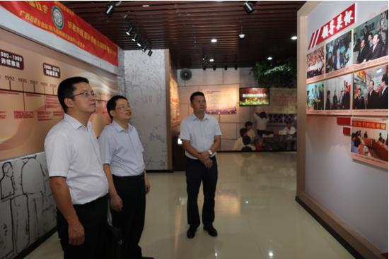 自治区财政厅综合处处长肖东海(左一)在广西福彩中心主任杜波(左二)、书记蓝挺(右一)陪同下参观广西福彩文化展示馆