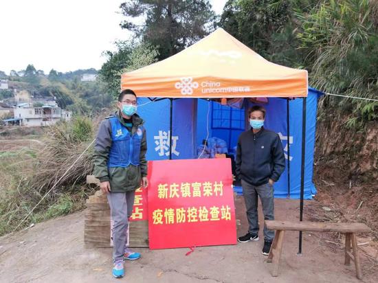 疫情防控检查一线的彭景亮(左)
