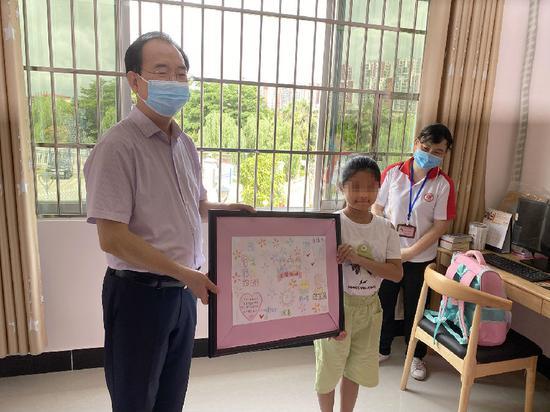 (图为2020年6月1日,自治区民政厅党组书记、厅长朱学庆到钦州市儿童福利院开展慰问活动,他勉励小芳好好学习,快乐生活。)