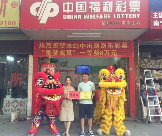 图为:南宁福彩工作人员为中奖投注站业主(右)颁发中奖牌匾及奖励金