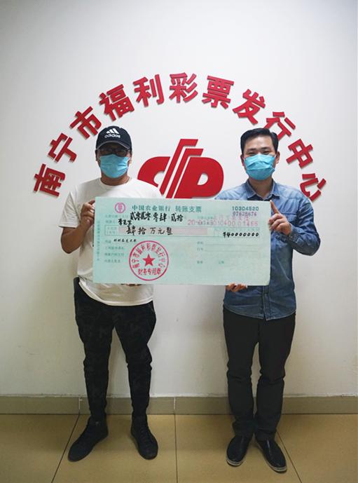 图为:南宁市福彩中心工作人员为李先生(左)颁奖