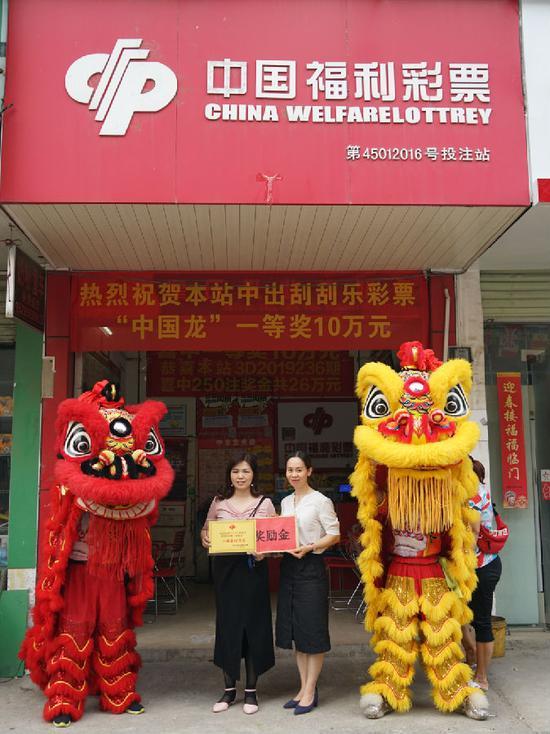 图为南宁市福彩中心工作人员为中奖投注站业主(左)颁发牌匾与奖励金