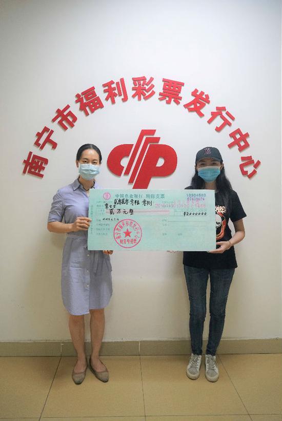 图1:福彩中心工作人员为覃女士(右)颁奖