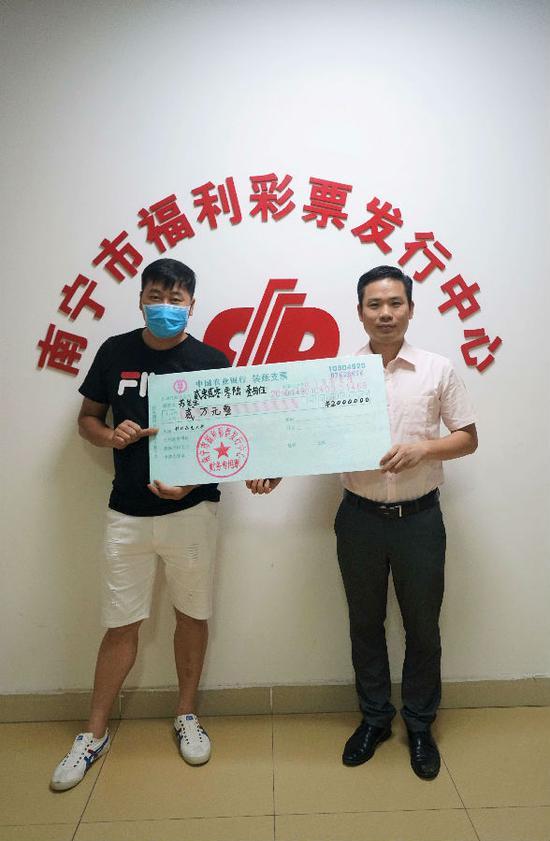 图2:福彩中心工作人员为苏先生(左)颁奖