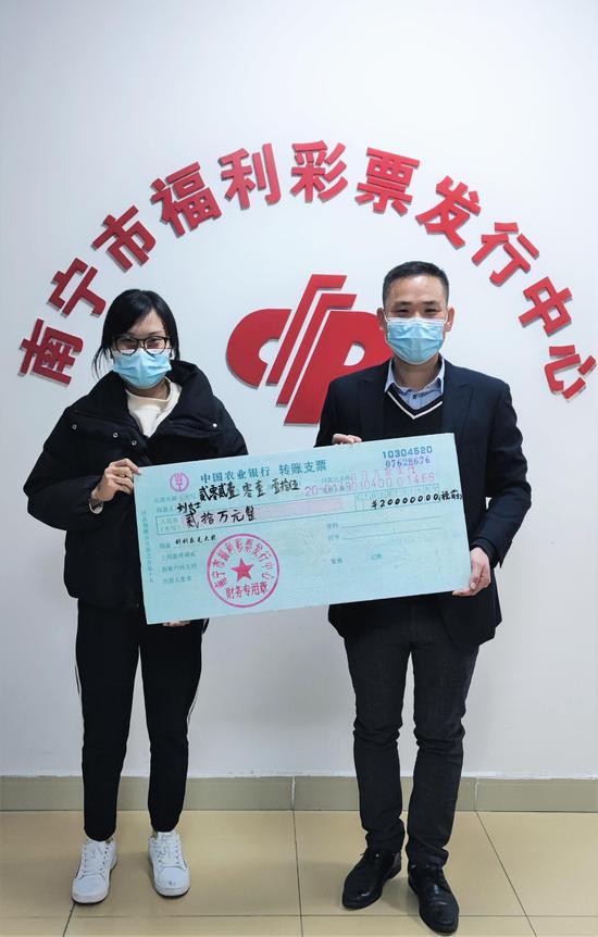 图为:市福彩中心工作人员为刘女士颁奖